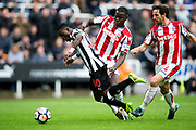 Newcastle United midfielder Christian Atsu (#30) bursts into the penalty area under pressure from Stoke City defender Kurt Zouma (#6) and Stoke City midfielder Joe Allen (#4) during the Premier League match between Newcastle United and Stoke City at St. James's Park, Newcastle, England on 16 September 2017. Photo by Craig Doyle.