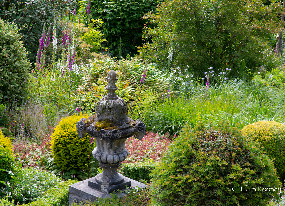 An aerial view of a carved stone urn surrouned by dense planting and viewed from the Belvedere in the Laskett Gardens. Much Birch, Herefordshire, UK