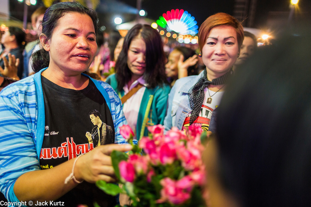19 JANUARY 2014 - BANGKOK, THAILAND:  Members of the audience buy roses to present to mor lam performers during a mor lam show in Khlong Tan Market in Bangkok. Mor Lam is a traditional Lao form of song in Laos and Isan (northeast Thailand). It is sometimes compared to American country music, song usually revolve around unrequited love, mor lam and the complexities of rural life. Mor Lam shows are an important part of festivals and fairs in rural Thailand. Mor lam has become very popular in Isan migrant communities in Bangkok. Once performed by bands and singers, live performances are now spectacles, involving several singers, a dance troupe and comedians. The dancers (or hang khreuang) in particular often wear fancy costumes, and singers go through several costume changes in the course of a performance. Prathom Bunteung Silp is one of the best known Mor Lam troupes in Thailand with more than 250 performers and a total crew of almost 300 people. The troupe has been performing for more 55 years. It forms every August and performs through June then breaks for the rainy season.              PHOTO BY JACK KURTZ