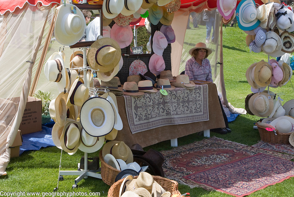 Woman selling hats from tent stall during garden  event at Helmingham Hall, Suffolk, England