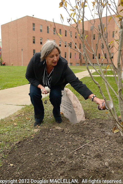 Nancy Myers sprinkles some of Tedfred Myer's ashes on a tree memorial on the northwest side of  the School of Dramatic Art. Tedfred, a longtime faculty member,  died earlier in the year. The Myers family as well as many of Tedfred's fellow faculty and other friends attend the brief but emotional memorial event.
