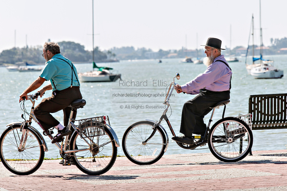 Amish men ride bicycles along the waterfront Sarasota, Florida