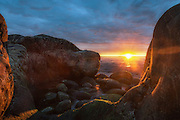 Sunset behind rocks by the ocean | Solnedgang bak berg ved havet.