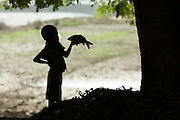 Young boy holding a fish in silhouette, Ayeryarwady River Jetty, Mandalay