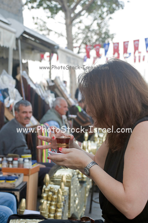 Turkey, Istanbul, Shoeshine stand female client drinking hot Turkish tea while waiting for to having her shoes polished