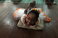 A girl stretches during her ballet class at the 'Ballet Santa Teresa' academy in Rio de Janeiro August 15, 2012. 'Ballet Santa Teresa', a non-governmental organization (NGO) gives children who live in areas with social risk, some suffering domestic violence, free ballet classes and other activities as a part of socio-cultural integration project.  Photo by: Pilar Olivares