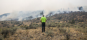 A resident of Omak watches wildfire creep down towards his neighbor's property off Vic Smith Road west of Conconully Road in central Washington Friday August 21, 2015. Neighbors and friends had been watching the property for the homeowner, who was away at work.<br />