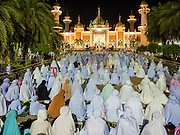 18 JUNE 2015 - PATTANI, PATTANI, THAILAND: Women sit on the plaza in front of Pattani Central Mosque during Ramadan services. Thousands of people come to Pattani Central Mosque in Pattani, Thailand, to mark the first night of Ramadan. Ramadan is the ninth month of the Islamic calendar, and is observed by Muslims worldwide as a month of fasting to commemorate the first revelation of the Quran to Muhammad according to Islamic belief. This annual observance is regarded as one of the Five Pillars of Islam. Islam is the second largest religion in Thailand. Pattani, along with Narathiwat and Yala provinces, all on the Malaysian border, have a Muslim majority.     PHOTO BY JACK KURTZ