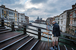 Painter on the Ponte dell Accademia over the Grand Canal looking towards the Basilica di Santa Maria della Salute in Venice, Italy.<br />
