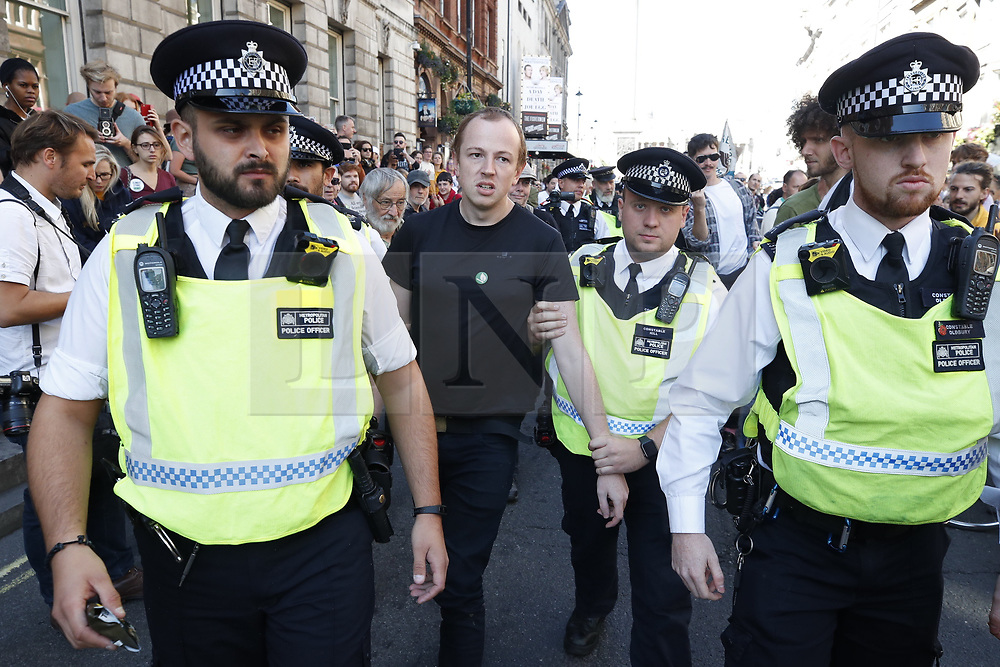 © Licensed to London News Pictures. 20/09/2019. London, UK. A activist taking part in the Global Climate Strike demonstration is detained by police after siting down in the road near Trafalgar Square. Thousands of similar actions are taking place all over the UK and the rest of the world. Photo credit: Peter Macdiarmid/LNP