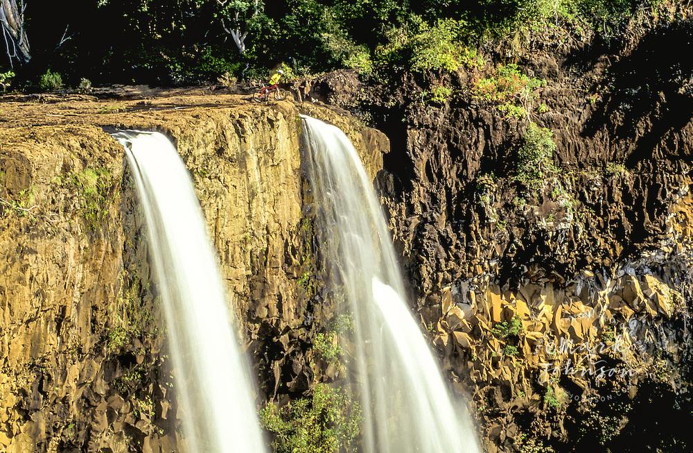 USA, Hawaii, Kauai, man with mountain bike peering over a waterfall.  MR available