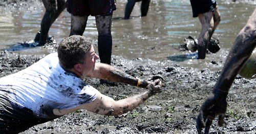 After a while, the court becomes more of a lake, with a very muddy, sticky bottom, but that doesn't deter many players from going for the ball during MuddyGras, the 20th annual mud volleyball for Epilepsy at Wegerzyn Gardens MetroPark in Dayton, Saturday, July 10, 2010.