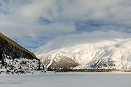 Storm clouds clear to reveal Maynard Mountain overlooking Portage Lake in Southcentral Alaska. Winter. Afternoon.