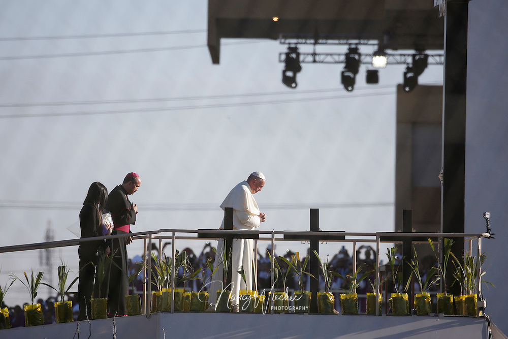 Pope Francis prays overlooking the U.S.-Mexico border before celebrating Mass Feb. 17 in Ciudad Juarez, Mexico. About 550 guests situated on a levee north of the Rio Grande took part in the Mass. (CNS photo/Nancy Wiechec) (View is through the border fence from El Paso)