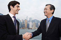 Two business men shaking hands office buildings in background