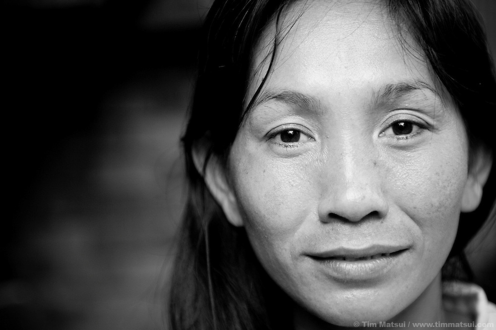 """Wue, a prostitute living in a slum where """"Acting for Women in Distressing Situations"""" (AFESIP) conducts outreach and provides services, in Phnom Penh, Cambodia. Wue, 30, was previously a small business owner but turned to prostitution as a result of her economic situation. The slum's permanent structure, a decaying four story building known simply as 'The Building', was built in the 1960's as transitional housing and now hosts a shantytown where many of the city's poor live, including many prostitutes, and is believed to have the highest rate of HIV infection in the city. AFESIP hands out free condoms, instructs prostitutes on HIV prevention, and conducts outreach in case the prostitutes need medical services, choose to leave their profession, or can report on cases of sex trafficking. AFESIP offers housing, education, training, and counseling for women who are victims of sex trafficking, worked as prostitutes, or are escaping domestic violence. Founded by Somaly Mam, who herself was once a prostitute and victim of trafficking and domestic abuse, AFESIP has three facilities in Cambodia and works with other NGO's to provide long term care for the women."""