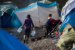 © Licensed to London News Pictures. 23/01/2016. Dunkirk, France. A young woman carrying water as her mother washes outside a tent  on the day that Leader of the Labour Party JEREMY CORBYN visited a temporary camp in Dunkirk, France, where thousands of migrants and refugees attempting to reach the UK are currently living. Photo credit: Ben Cawthra/LNP
