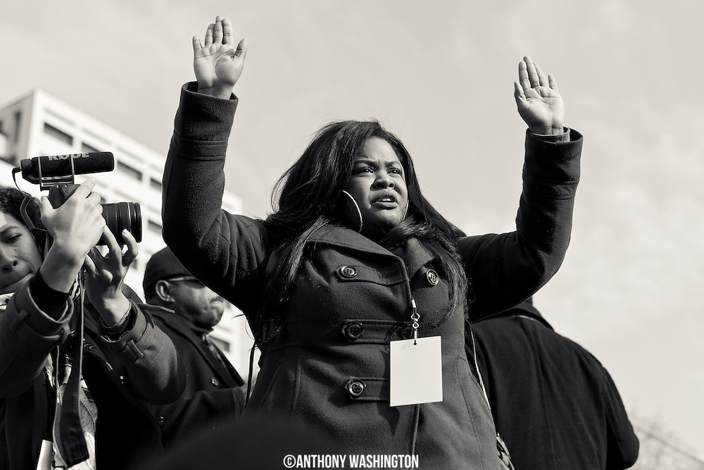 Johnetta Elzie of St. Louis, Mo. holds her hands up in protest on stage at the Justice For All March in Washington, DC on Saturday, December 13, 2014.