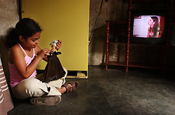 Regina Jose, 9, plays with one of the few toys she has in her home.  She typically spends the day at home with her family playing and watching TV. Nearly two months after a national strike devastated Venezuela's economy, many people are still unable to find work.  Venezuela has a poverty rate of 80%.