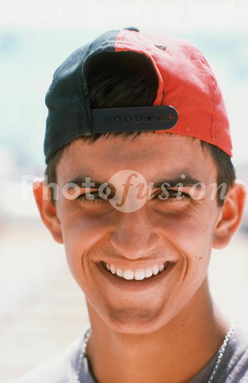 Portrait of teenage boy wearing baseball cap and smiling,
