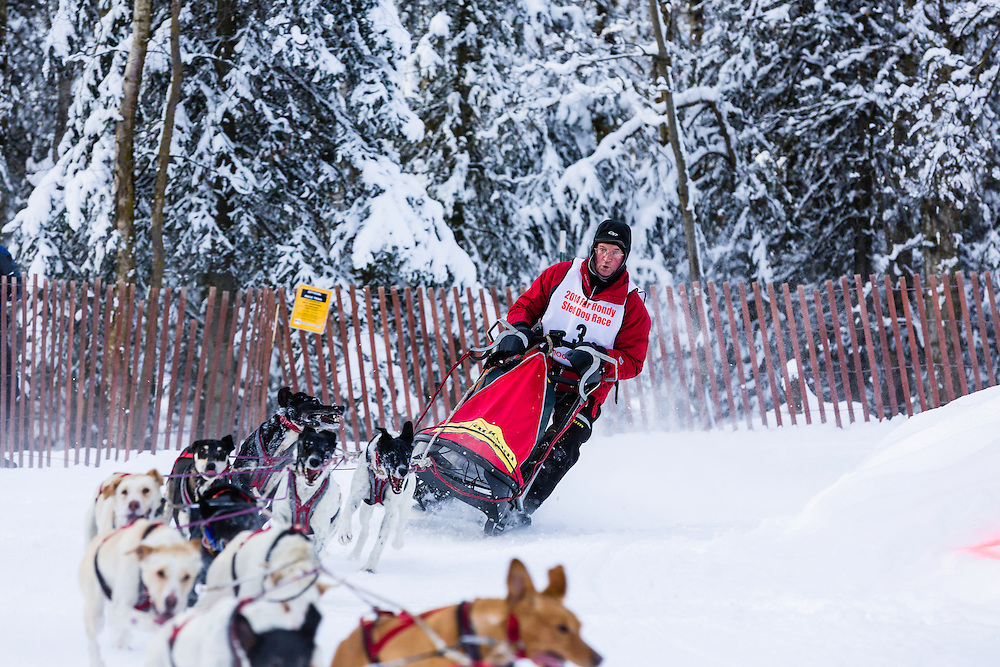 Musher Ken Chezik competing in the Fur Rendezvous World Sled Dog Championships at Goose Lake Park in Anchorage in Southcentral Alaska. Winter. Afternoon.