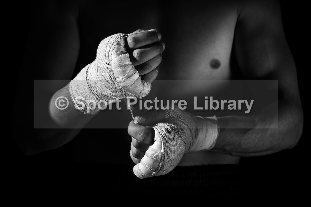Boxer applying hand wraps.