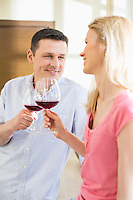 Happy couple toasting red wine glasses in kitchen