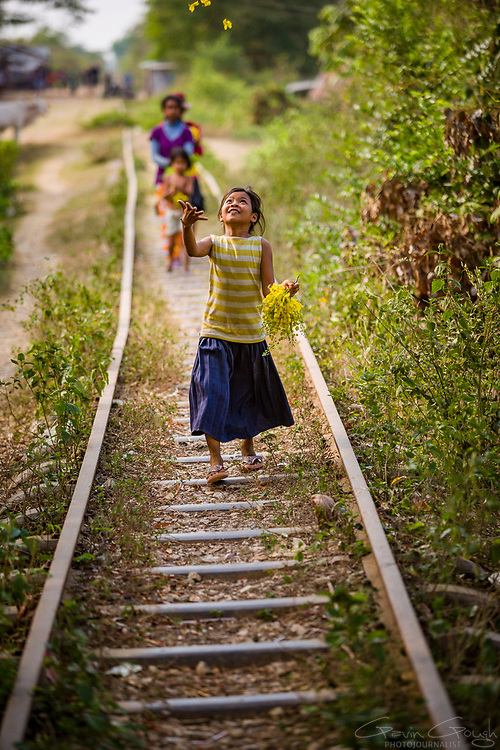 """Children play along the tracks of the now disused """"Bamboo Railway""""."""