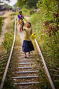 "Children play along the tracks of the now disused ""Bamboo Railway""."