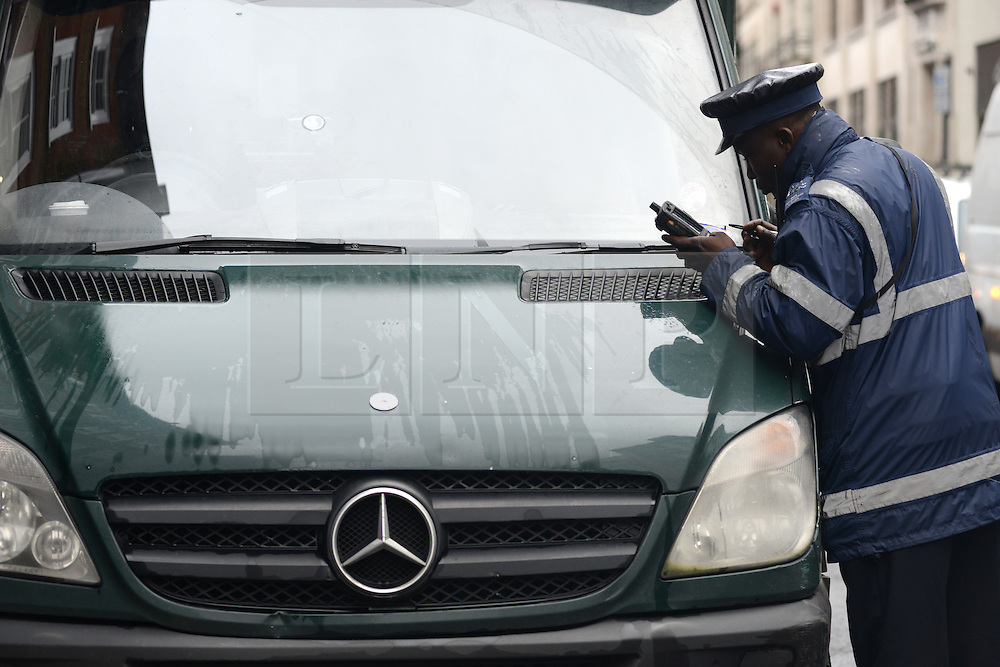© Licensed to London News Pictures.17/01/2014. London, UK A traffic warden is putting parking ticket on windscreen of lorry on Wardour Street in Soho, London. Wardour Street is the most ticketed road in the country, according to figures obtained under the Freedom of Information Act. Between January and October last year 5,143 tickets were issued, raising up to £410,000..Photo credit : Peter Kollanyi/LNP