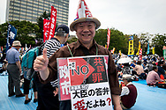 A old man holds a placard around his neck during the May Day rally in Tokyo on Monday, May 1, 2017, Thousands people participate demanding higher pays among other issues. 01/05/2017-Tokyo, JAPAN