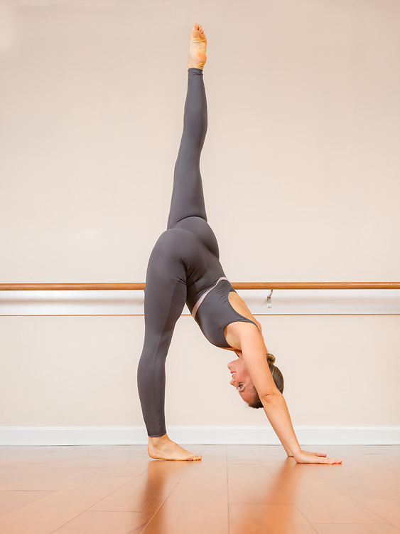 Woman performs healthy, flexibility, yoga position demonstration.