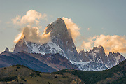 The afternoon sun lights a few clouds still clinging to Mount Fitzroy. View from El Chalten.