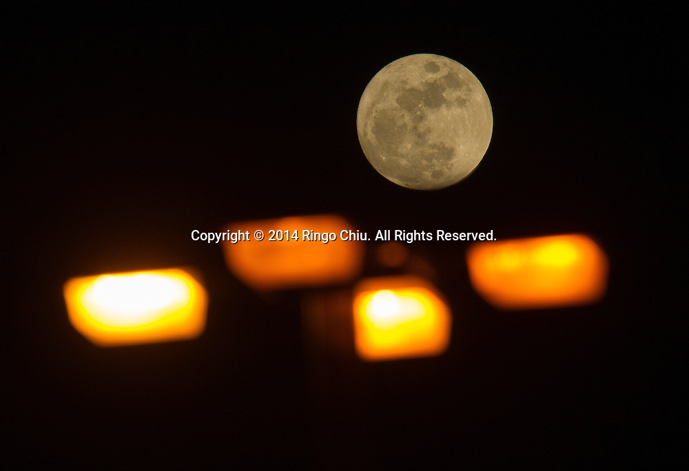 The first full moon (know as Wolf moon) of the year is seen behind a street lamp on Sunday, January 4, 2015 in Los Angeles, California. (Photo by Ringo Chiu/PHOTOFORMULA.com)
