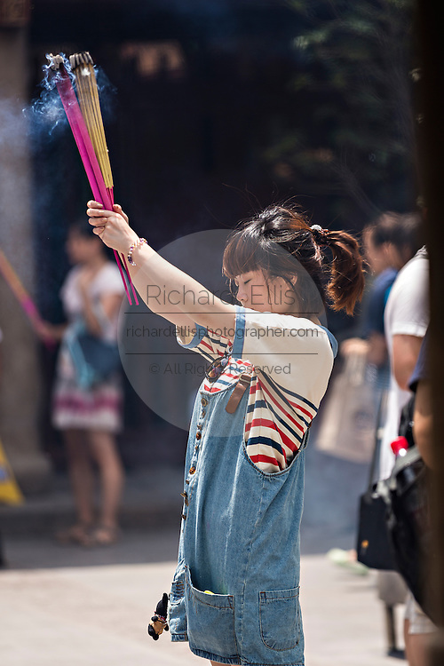 A woman prays at Chenghuang Miao or City God Temple in Yu Yuan Gardens bazaar Shanghai, China