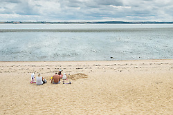 A family enjoying themselves on the beach at Thorney Bay on Canvey Island, Essex.