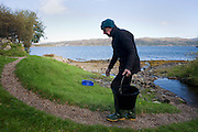 Hermit Tom Leppard fetches fresh water from a nearby stream at his secret hideaway shelter on Skye, Scotland.