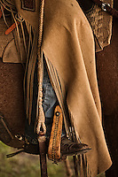 Western cowgirl attire on horseback; chaps, jeans, boots, wood stirrup. Petaluma, California, USA.