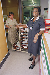 Ward waitress and nursing auxiliary preparing to serve patient meals,
