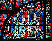 Julienne, widow of Senator Alexander, founder of the Jerusalem church dedicated to St Stephen, asks bishop Cyril permission to take her husband's body to Constantinople to be buried near St Stephen. Section of the widow claiming the body of her dead husband, 1220-25, from the Life of St Stephen and transferral of his relics window in the ambulatory of Chartres Cathedral, Eure-et-Loir, France. This window, unusually dominantly red in colour, tells the story of the life of St Stephen, the first Christian martyr, who died c. 36 AD and whose relics are held at Chartres. It is situated in the chapel dedicated to martyrs. Chartres cathedral was built 1194-1250 and is a fine example of Gothic architecture. Most of its windows date from 1205-40 although a few earlier 12th century examples are also intact. It was declared a UNESCO World Heritage Site in 1979. Picture by Manuel Cohen