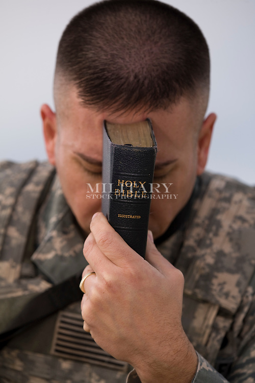 Soldier studies the bible and prays.  The role of religion and faith among members of the US armed forces is strong.  This image complies with US DoD regulations for use in advertising.