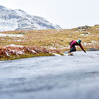 A photograph of a skateboarder on a road during winter in the Lake District, Cumbria, England