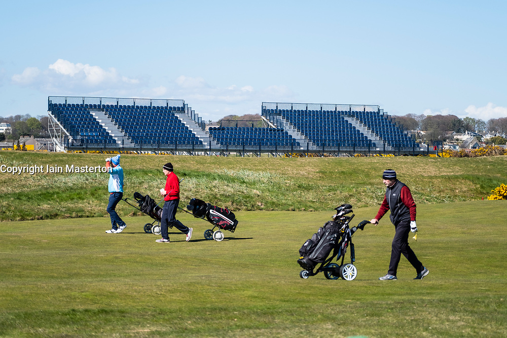 Golfers on fairway with spectator stands under construction to rear at Carnoustie Golf Links in Carnoustie, Angus, Scotland, UK. Carnoustie is venue for the 147th Open Championship in 2018.