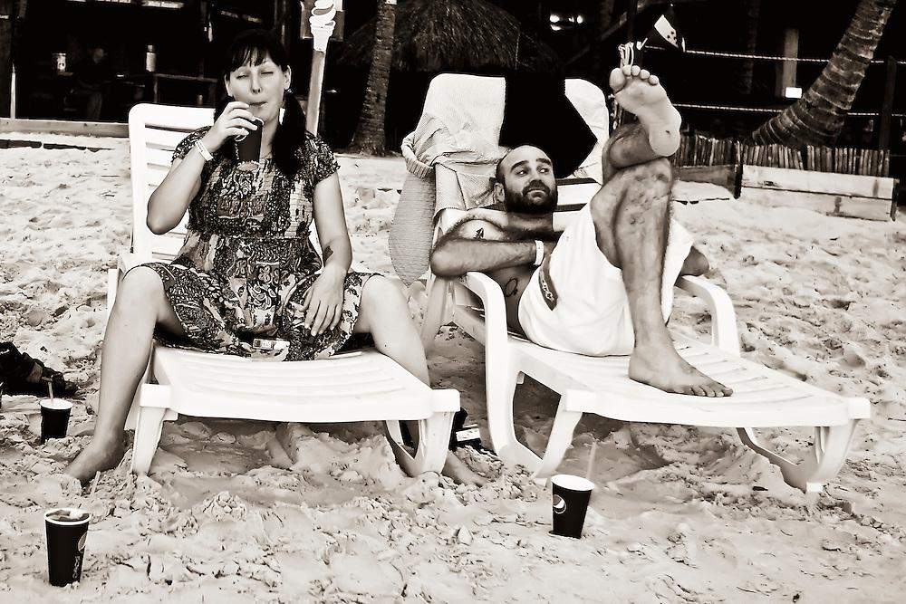 Drunk couple enjoys another drink on beach in Roatan, Honduras. Copyright 2010 Reid McNally.