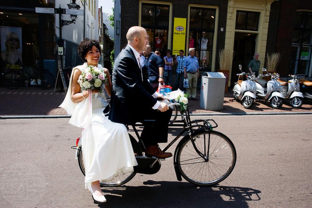 Lola en Dennis komen op hun trouwdag met de fiets naar het stadhuis in Leiden