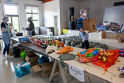 Volunteers pack dry food and vegetables into packets as they prepare food parcels at a church, to be distributed to Vanwyk'svlei in Wellington, Western Cape, South Africa.(Picture: JULIAN GOLDSWAIN)