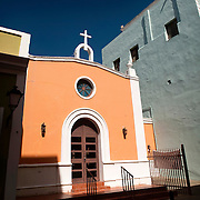 Scenic Old San Juan, Puerto Rico, originally founded in 1508 by the Spanish explorer Juan Ponce de León, is today a thriving carribean outpost of the United States.  The brightly -painted facades of the historic buildings, such as this orange - walled church, make the city an architectural gem and add tropical flair.<br /> <br /> This is a panoramic composite.