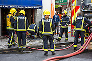 Firefighters from the London Fire Brigade respond to an emergency on Church Street, Stoke Newington, London.  They have been called out due to an explosion in the basement of a shop.  The London Fire Brigade is the 4th largest fire-service in the world.  The firefighter in the middle of the image is a woman. As of 2012 there are 257 female firefighters in the London Fire Brigade.  As of March 2007 the proportion of operational firefighters in the UK who were women was 3.1%.