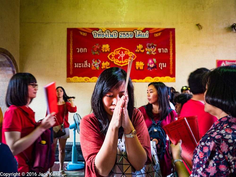 """07 FEBRUARY 2016 - BANGKOK, THAILAND: People pray during Chinese New Year ceremonies at Wat Mangon Kamlawat in Bangkok. Chinese New Year, also called Lunar New Year or Tet (in Vietnamese communities) starts Monday February 8. The coming year will be the """"Year of the Monkey."""" Thailand has the largest overseas Chinese population in the world; about 14 percent of Thais are of Chinese ancestry and some Chinese holidays, especially Chinese New Year, are widely celebrated in Thailand.        PHOTO BY JACK KURTZ"""