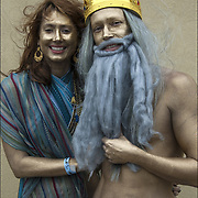 Mermaid Parade couple wearing gold face paint, he is going as Neptune the god of the sea  <br /> before the start of the parade in Coney Island.